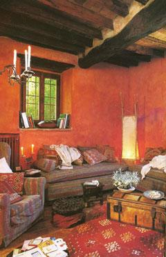 Az őszi hangulatot színeivel és rusztikus anyagaival is remekül példázza ez a gerendamennyezetes nappali. Az antikolt vörös fal meleg hátteret ad az öreg bútoroknak. A szederpiros és kékeslila csíkos ülőbútor színei is az őszi paletta alkotói. A kukoricasárga lámpaernyő jól kiegészíti és ellenpontozza is a sötét árnyalatokat.